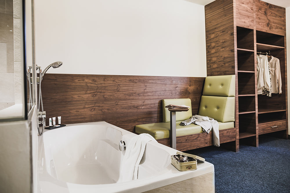Bathtub with workstation in the background in the Junior Suite at the Cocoon Hotel Sendliger Tor Munich