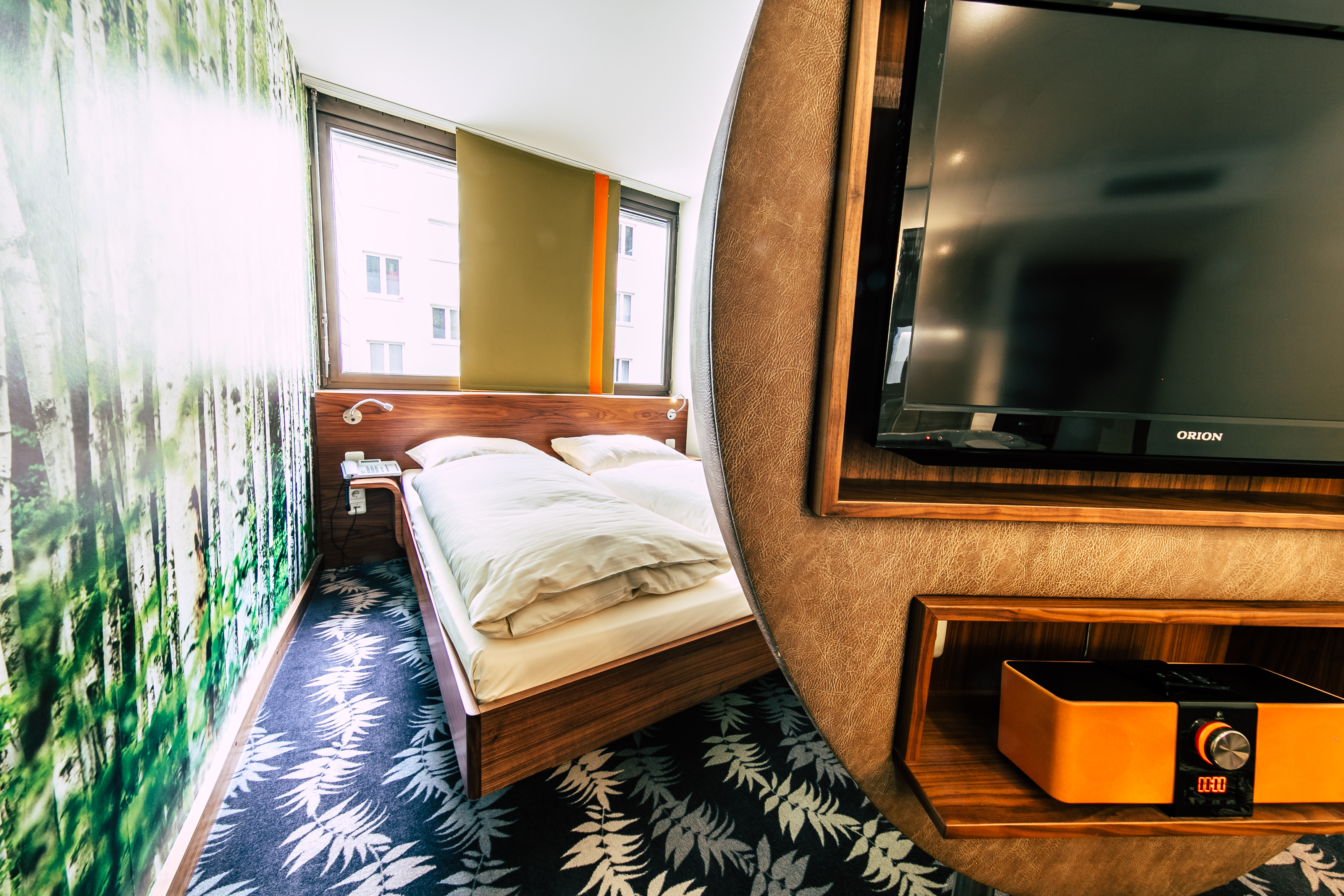 View into a double room in the Cocoon Hotel Stachus with a television integrated into a room divider.