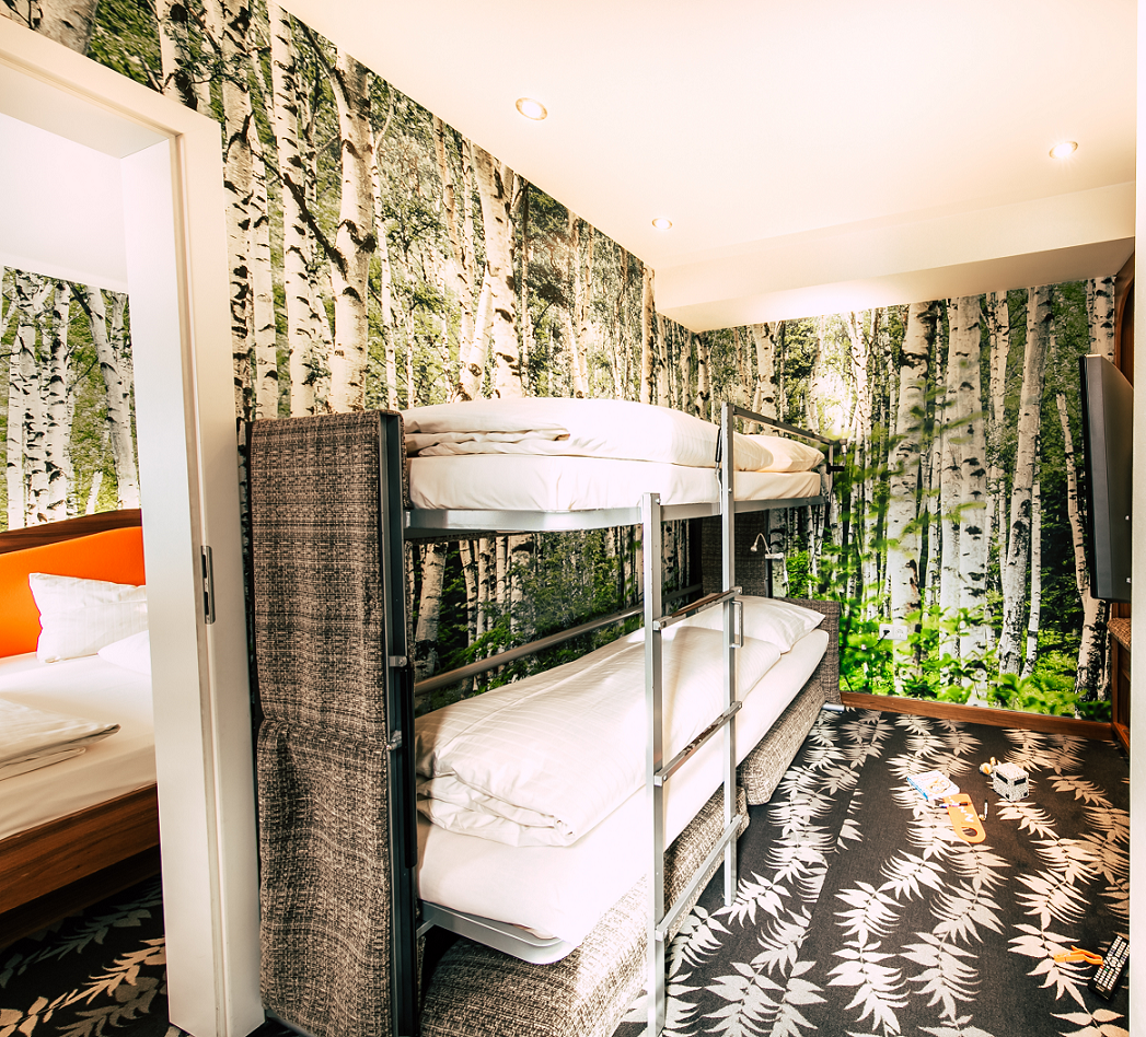 View into a room with four beds in the Cocoon Hotel München Stachus with a double bed and a bunk bed - on the wall you can see a birch wood wallpaper